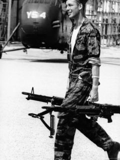 Yankee Papa 13 Helicopter Crew Chief James Farley Carrying a Pair of M 60 Machine Guns Premium Photographic Print by Larry Burrows