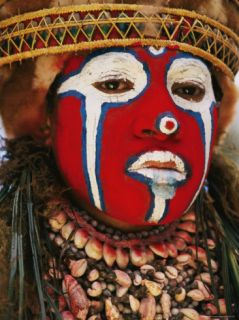 A Tribal Woman Clad with Shell Necklaces and Bright Face Paint Photographic Print by Jodi Cobb