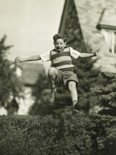 Teenage Boy (13 14) Leaping Over Hedge, Low Angle View Photographic Print by George Marks