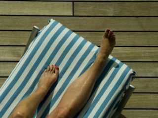 Womans Legs on a Striped Cushion on the Deck of a Cruise Ship Photographic Print by Todd Gipstein